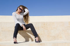 Cute young brunette girl sitting outdoor. Blue sky Royalty Free Stock Images