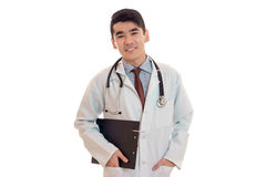 Cute young brunette male doctor with stethoscope in uniform smiling on camera isolated on white background. Cute young brunette male doctor with stethoscope in Royalty Free Stock Photo
