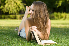 Cute young brunette in the park reading. Royalty Free Stock Image