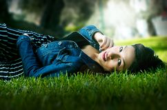 Cute young brunette reclining on the grass in the park stock photos