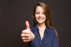 Cute young brunette showing big thumbs up. Stock Photo