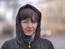 Cute young brunette woman in a hood on a city street looking into the camera stock image