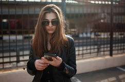 Cute young brunette woman walk and using smartphone Stock Photos