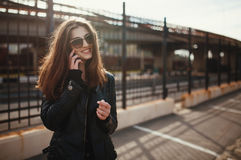 Cute young brunette woman walk and using smartphone Stock Photo