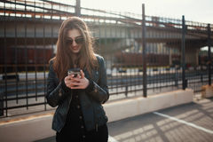 Cute young brunette woman walk and using smartphone Royalty Free Stock Images