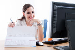 Cute young businesswoman checking her calendar Royalty Free Stock Image
