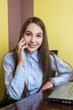 Cute young businesswoman smiling and talking on the phone in the office. Royalty Free Stock Photos