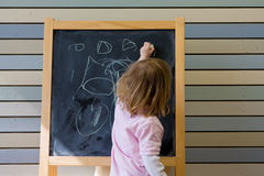 Cute young caucasian boy writing on a blackboard Stock Photography