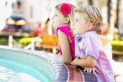 Cute Young Caucasian Brother and Sister Enjoying a Fountain At stock photo