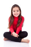 Cute young caucasian girl seated on the floor Royalty Free Stock Images