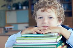 Cute young Caucasian schoolboy lying on top of a pile of books at classroom. royalty free stock image