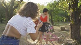 Cute young caucasian woman with short hair posing with her bicycle while her friend taking a photo in the garden or park. Attractive young caucasian woman with stock video