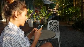 Cute Young Caucasian Woman Sitting in a Cafe and Writing Message on the Phone. stock video