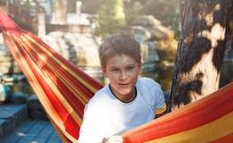 Cute young cheerful boy in white t shirt lies on hammock outdoor, rests at vacation concept. Summer stock photo