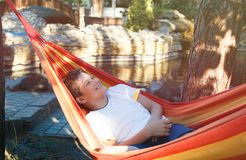 Cute young cheerful boy in white t shirt lies on hammock outdoor, rests at vacation concept. Summer stock images