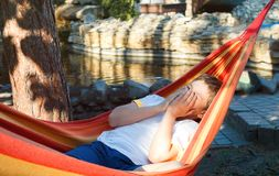 Cute young cheerful boy in white t shirt lies on hammock outdoor, rests at vacation concept. Summer royalty free stock photo