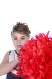 Cute young cheerleader holding large red pompom Stock Image