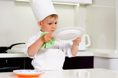 Cute young chef checking his dinner plates Royalty Free Stock Photos