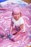 Cute young child covered in paint. Laughing cute girl holding empty bottle while soaking wet in pink paint from head to toe. She is seated in middle of large royalty free stock photo