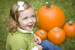 Cute Young Child Girl Enjoying the Pumpkin Patch. Royalty Free Stock Photos