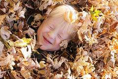 Cute Young Child Laying in Pile of Fall Leaves Royalty Free Stock Photos