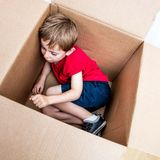 Cute young child resting, playing in cardboard box for imagination royalty free stock photography