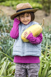 Cute young child smiling after picking organic squash from garden Stock Images