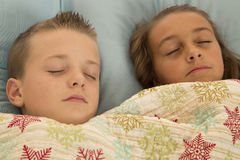 Cute young children asleep with a pillow and blanket royalty free stock photos