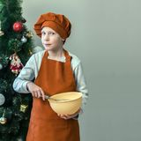 A cute young cook in orange clothes is holding a cup for stirring food while cooking dough on the background of a Christmas tree. Stock Photo