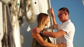 Beautiful couple is having a good time on board a yacht on vacation. Cute young cople is spending romantic evening aboard the yacht together. Woman softly stock video