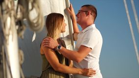 Beautiful couple is having a good time on board a yacht on vacation. Cute young cople is spending romantic evening aboard the yacht together. Woman softly stock video footage
