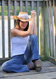 Cute young country girl sitting on a deck Royalty Free Stock Photo