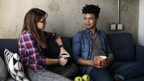 Cute young couple, attractive caucasian girl and her handsome mulatto boyfriend sitting on the couch, drinking tea stock video footage