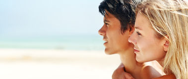Cute young couple at the beach looking away Royalty Free Stock Photography