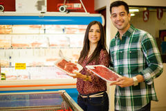 Cute young couple buying meat Stock Images