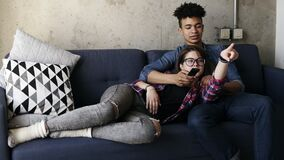 Cute young couple on the couch, attractive caucasian girl lying on her handsome mulatto boyfriend`s laps. He is trying stock video footage