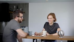 Cute young couple drinking coffee in kitchen. Husband and wife are sitting side by side in a modern interior. stock video