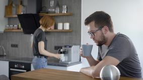 Cute young couple drinking coffee in kitchen. The wife made a big cappuccino stock video footage