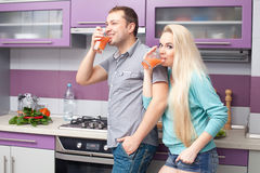 Cute young couple drinking fresh citrus juice. Portrait of a cute young couple drinking fresh citrus juice together at home (kitchen). Wife is pregnant. Indoor stock photo