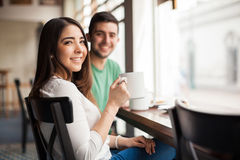 Cute young couple drinking some coffee. Beautiful girlfriend and her boyfriend relaxing and enjoying a cup of coffee in a restaurant Stock Image