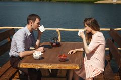 Cute couple drinking tea outdoors. Cute young couple drinking tea outdoors, happy lovers have a good time on pier with a cup of tea royalty free stock photography