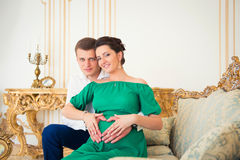 Cute young couple embracing tenderly pregnant tummy. Royalty Free Stock Image