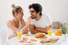 Cute young couple enjoying their breakfast together stock images