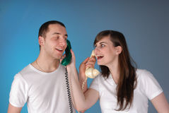 Cute young couple exchange telephones. Cute young couple having fun conversing on telephones stock photo