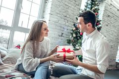Merry Christmas and Happy Holidays! Cute, young couple exchanging Christmas presents on Christmas morning royalty free stock photos