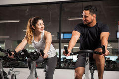 Cute young couple flirting at a gym. Beautiful young Hispanic women flirting and talking to a guy while they both do some spinning at a gym royalty free stock photography
