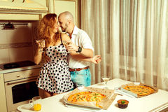 Cute young couple flirting at a party with alcohol and pizza Stock Photography