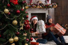 Cute young couple guessing at their Christmas gifts holding a bo Stock Photos