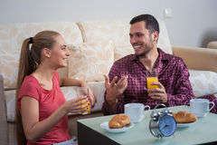 Cute young couple having breakfast, eating croissants, drinking orange juice. Royalty Free Stock Photography