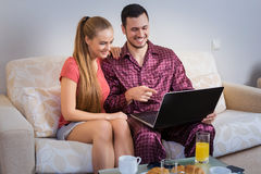Cute young couple having breakfast, in front of laptop computer Stock Images